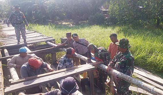 Polisi dan TNI Bersama Warga Perbaiki Jembatan