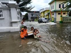 Keceriaan Anak-anak Bermain di Genangan Banjir Pekanbaru